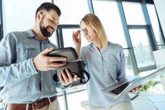 2 жизнерадостных коллеги смотря шлемофон внутренности открытый VR стоковая фотография
