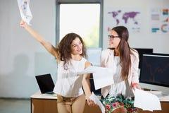2 жизнерадостных красивых молодых девушки дела в офисе Стоковая Фотография