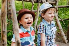 2 жизнерадостных мальчика в шляпах сидя на стенде в парке Стоковые Фото