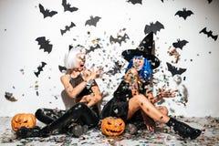2 жизнерадостных молодой женщины в кожаных костюмах хеллоуина Стоковые Фотографии RF