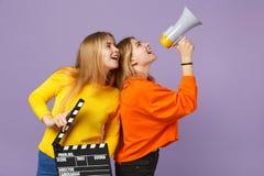 2 жизнерадостных молодых белокурых девушки сестер близнецов держат классическое черное clapperboard создания фильма, клекот на из стоковое изображение
