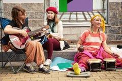 3 жизнерадостных музыканта улицы играя музыку на тротуаре Стоковые Изображения