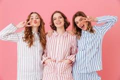 3 жизнерадостных одежды отдыха женщин 20s нося имея потеху на Стоковые Изображения
