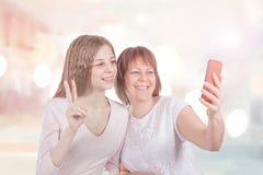 2 жизнерадостных подруги делают selfie с телефоном Стоковые Фото