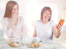 2 жизнерадостных подруги смотрят фото в smartphone Стоковое фото RF