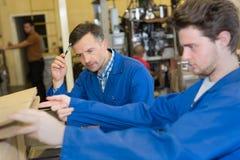 2 жизнерадостных сотрудника работая на машине в мастерской Стоковая Фотография