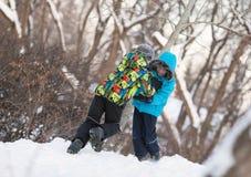 2 жизнерадостных счастливых мальчика играя в парке зимы, Стоковые Изображения