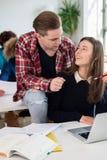 2 жизнерадостных тысячелетних студента смеясь над пока сидящ совместно Стоковые Фотографии RF
