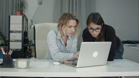 2 жизнерадостных усмехаясь молодых бизнес-леди работая на компьтер-книжке Стоковая Фотография RF