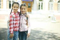 2 жизнерадостных школьницы с schoolbags Стоковая Фотография RF