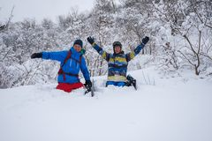 2 жизнерадостных snowboarders сидят в глубоком снеге Стоковые Фотографии RF