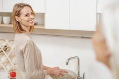 Жизнерадостная дама делая домашнее хозяйство для любящего родителя Стоковое Фото