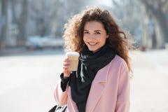 Жизнерадостная дама нося розовое пальто идя в город Стоковые Фото