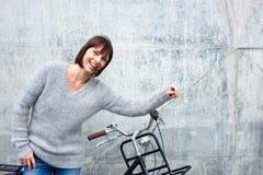 Жизнерадостная более старая женщина с велосипедом стоковая фотография rf
