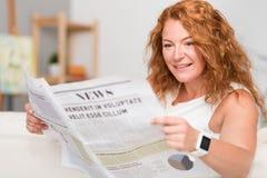 Жизнерадостная газета чтения взрослой женщины Стоковые Изображения