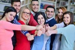 Жизнерадостная группа в составе студенты усмехаясь на камере с большими пальцами руки вверх, успехом и уча концепцию Стоковые Фотографии RF