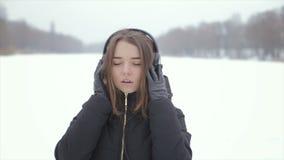 Жизнерадостная девушка в наушниках зимы слушая к музыке, стоя в снеге видеоматериал