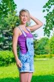 Жизнерадостная девушка в прозодеждах джинсовой ткани представляя в парке Стоковая Фотография RF