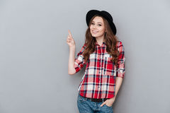 Жизнерадостная девушка в рубашке шотландки указывая палец вверх на copyspace Стоковое Изображение RF