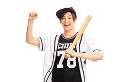 Жизнерадостная девушка в jersey бейсбола держа летучую мышь и показывать Стоковые Изображения