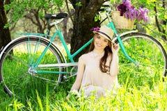 жизнерадостная девушка Горизонтальная съемка красивой молодой женщины в платье и шляпе регулируя шляпу и усмехаясь пока сидящ на  Стоковая Фотография RF