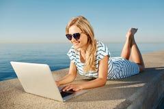 Жизнерадостная девушка лежа на лете на пляже около моря и беседах к Стоковые Фото
