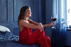 Жизнерадостная девушка держа стекло красного вина и смотря через th Стоковое Изображение