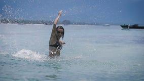 Жизнерадостная девушка околпачивая вокруг пока стоящ около пляжа Смешное милое брюнет на малой глубине в ходах океана сток-видео