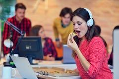 Жизнерадостная девушка офиса наслаждаясь пиццей на обеденном времени Стоковое Изображение