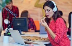 Жизнерадостная девушка офиса наслаждаясь пиццей на обеденном времени Стоковые Фото