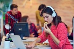 Жизнерадостная девушка офиса наслаждаясь пиццей на обеденном времени Стоковая Фотография
