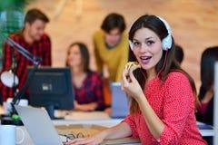 Жизнерадостная девушка офиса наслаждаясь пиццей на обеденном времени Стоковые Фотографии RF