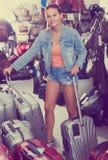 Жизнерадостная девушка подростка выбирая новую большую пластичную сумку багажа стоковые фото