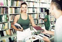 Жизнерадостная девушка получая помощь с выбором книги стоковые фото