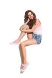 Жизнерадостная девушка сидя на белой стене Стоковая Фотография RF