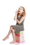 Жизнерадостная девушка сидя на книгах и показывать Стоковые Изображения RF