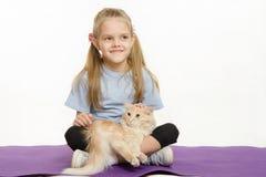 Жизнерадостная девушка сидя на половике с котом Стоковое Изображение RF