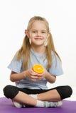 Жизнерадостная девушка сидя с апельсином на половике спорт Стоковые Фотографии RF