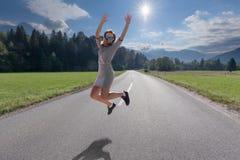 Жизнерадостная девушка скача и имея потеха на дороге стоковое фото