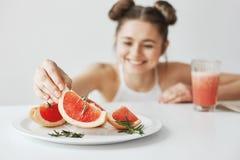 Жизнерадостная девушка усмехаясь принимающ кусок грейпфрута от плиты сидя на таблице над белой стеной Здоровая концепция фитнеса Стоковые Фото