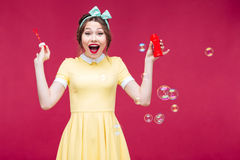 Жизнерадостная девушка pinup смеясь над и имея потехой с пузырями мыла Стоковое Изображение