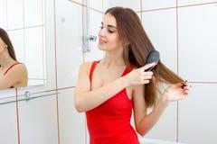Жизнерадостная женщина брюнет в красной футболке расчесывая волосы стоковые фото