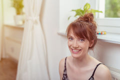Жизнерадостная женщина внутри дома смотря камеру Стоковые Изображения RF