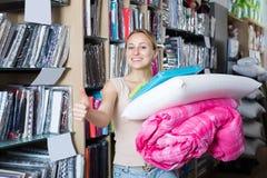 Жизнерадостная женщина выбирая одеяло и подушку Стоковые Фото