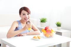 Жизнерадостная женщина выпивая апельсиновый сок стоковые изображения