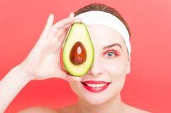 Жизнерадостная женщина держа половину авокадоа стоковые фотографии rf