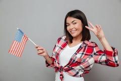Жизнерадостная женщина держа флаг США над серой стеной стоковое изображение rf