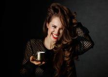 Жизнерадостная женщина держа чашку кофе на темной предпосылке Стоковые Изображения RF