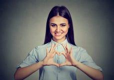 Жизнерадостная женщина делая знак сердца с руками Стоковые Изображения RF