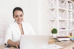 Жизнерадостная женщина используя компьтер-книжку Стоковые Фото